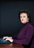 The aged woman in front of the monitor Royalty Free Stock Photography