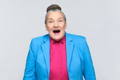 Aged woman have surprised face. Aged woman with surprised face. Portrait of handsome expressive grandmother with light blue suit and pink shirt standing with royalty free stock photography