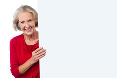 Aged woman holding blank ad board Royalty Free Stock Image