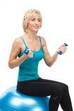 Aged woman holding dumbbells and smiling. Stock Photos