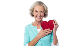 Aged woman holding a red valentine gift box Royalty Free Stock Images