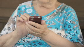 Aged woman holding a smartphone stock video footage