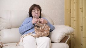 Aged woman knitting while sitting on sofa at home