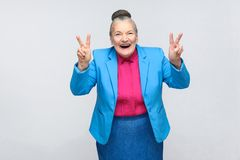 Aged woman laugh and showing peace or victory sign at camera. Aged woman laugh and showing peace or victory signat camera. Emotion and feelings. Portrait of royalty free stock photo