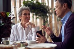 Aged woman listening male friend with interest. Enjoyable meetings. Waist up portrait of gray haired elegant lady listening with interest her male friend while stock photo