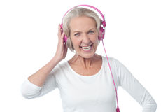 Aged woman listening to music Royalty Free Stock Image