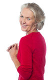 Aged woman looking over her shoulders Royalty Free Stock Images