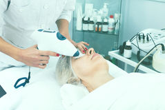 Aged woman making beauty procedures for face Royalty Free Stock Photo