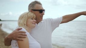 Aged woman and man hugging looking into the distance beach. stock video footage