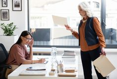 Aged woman is not satisfied with work of her subordinate. This is bad. Senior lady boss is standing near desk of her young assistant and holding folders while Royalty Free Stock Image