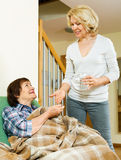 Aged woman offering pills and water to pensioner Royalty Free Stock Image