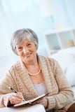Aged woman. Portrait of aged female looking at camera while making notes in notebook Royalty Free Stock Images