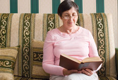 Aged woman reading a book. On sofa Stock Images