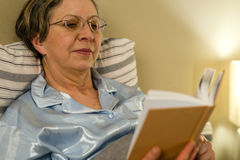 Aged woman reading book in residential home. Aged woman reading book in bed in residential home Stock Images