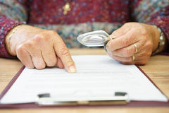 Aged woman reading document with magnifying galss Stock Images