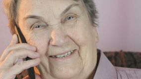 Aged woman 80s smiling talks on the mobile phone stock footage