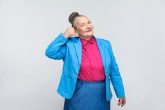 Aged woman showing call center sign. Portrait of handsome expressive grandmother with light blue suit and pink shirt standing with collected bun gray hair royalty free stock images