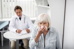 Aged woman sneezing and general practitioner looking at her stock photo