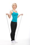 Aged woman standing on jumping rope. Stock Photos