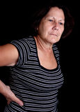 Aged woman suffering from back pain. On a black background with space for text Stock Photography