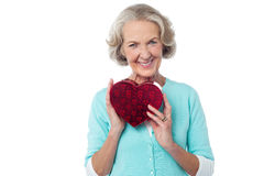 Aged woman symbolizing love, holding gift. Stock Photo
