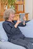 Aged woman with tablet pc. Relaxed and happy aged woman sitting with tablet pc on her sofa Royalty Free Stock Image