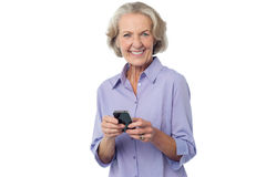 Aged woman texting on her mobile phone Royalty Free Stock Photos