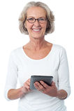 Aged woman with touch pad device. Senior citizen posing with tablet pc over white Stock Image