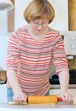 The aged woman unrolls dough Stock Image