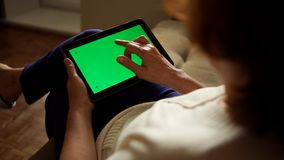 Aged woman using a digital tablet PC with green screen, back view. Aged woman using a digital tablet PC with green screen stock photography