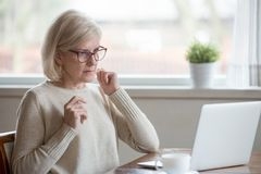 Aged woman using laptop confused seeing error message royalty free stock photos