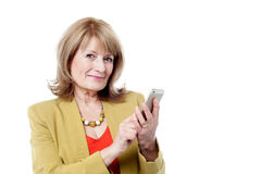 Aged woman using smart phone Stock Images