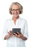 Aged woman using touch pad device. Senior citizen posing with tablet pc over white Stock Photography