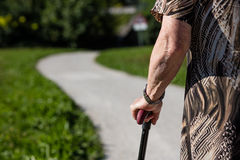 Aged woman walking with her stick Stock Photos