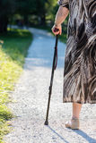 Aged woman walking with her stick. Old woman holding on to a cane walking outdoors Stock Photos