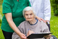 Aged woman in a wheelchair with medical assistance royalty free stock photo