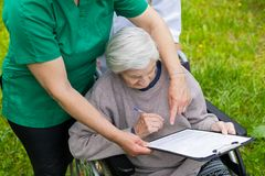 Aged woman in a wheelchair with medical assistance royalty free stock images