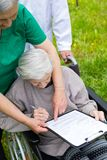 Aged woman in a wheelchair with medical assistance stock photos