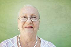 Aged woman with white hair smiling at camera Royalty Free Stock Images