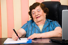 Aged woman writing on papers in office Stock Images
