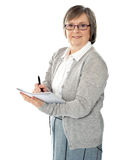 Aged woman writing on spiral notebook Stock Image