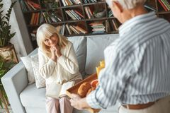 Senior couple together at home retirement concept breakfast. Aged women sitting on the coach and her husband brought her breakfast royalty free stock photo