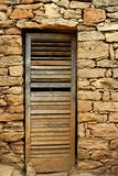 Aged wood door on masonry stone wall Royalty Free Stock Image