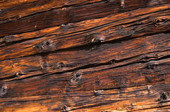 Aged wooden boards. Facing of wooden boards of a wall. Side of an old alpine refuge Royalty Free Stock Images