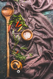 Aged wooden cooking spoon with spices, pepper mill and salt on crumpled tablecloth. Top view Stock Image