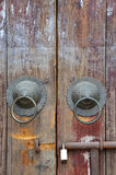 Aged wooden door with knocker and lock Royalty Free Stock Photos