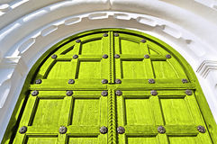 Aged wooden door with metal rivets and arch of white stone Stock Image