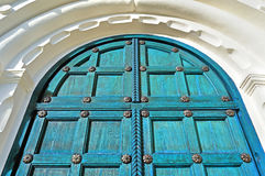 Aged wooden door with metal rivets and arch of white stone Royalty Free Stock Image
