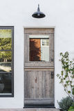 Aged wooden door to a white home Stock Image