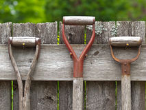 Aged wooden gardening tools hanging in a row on an old wooden fe Royalty Free Stock Photos